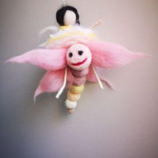 Hadita feliz con libélula de lana